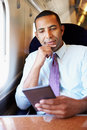 Homme d affaires commuting on train lisant un livre Photos stock