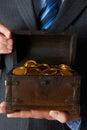 Homme d affaires holding wooden chest avec des pièces d or à l intérieur Photo stock