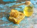 Honey background. Sweet honey in the comb . On rural wooden background. Glass bank with honey