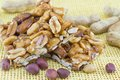 Honey bar with peanuts almonds and hazelnuts surrounded by roast Royalty Free Stock Photo