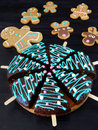 Honey cakes decorated as Christmas trees and gingerbread men and deers cookies in the background Royalty Free Stock Photo