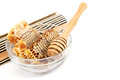 Honey comb in a glass bowl and wooden stick. Royalty Free Stock Photo