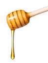 Honey dripping from wooden honey dipper isolated on white background Royalty Free Stock Photo