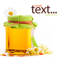 Honey in glass jar with flowers Royalty Free Stock Photo