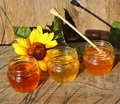 Honey in a glass jar with flowers on the wooden floor. Royalty Free Stock Photo