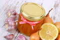 Honey in glass jar onion lemon and garlic healthy nutrition and strengthening immunity fresh organic on old wooden background Stock Photo