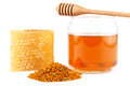 Honey in jar with dipper, honeycomb, pollen on isolated background Royalty Free Stock Photo