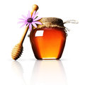 Honey jar with wood stick and pink flower Royalty Free Stock Image