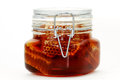 Honey pot a glass on white Stock Photography