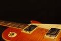Honey sunburst vintage electric rock guitar closeup on black background, with plenty of copy space. Selective focus. Royalty Free Stock Photo