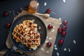 Honey on waffles with cherry berries on dark wooden background. Royalty Free Stock Photo