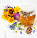 Honey and wild flowers on a wooden background Stock Images