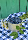 Honeyberry in old ladle with daisy flowers vertical still life honeysuckle berries and on checked tablecloth Royalty Free Stock Photos