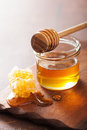 Honeycomb dipper and honey in jar on wooden background Royalty Free Stock Photo