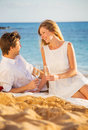 Honeymoon concept man and woman in love couple enjoying glass of champagne on tropical beach at sunset Stock Photography