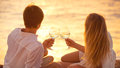 Honeymoon concept man and woman in love couple enjoying glass of champagne on tropical beach at sunset beautiful sunset light Stock Photo