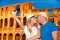 Honeymoon vacation in rome gentle loving couple kissing and taking picture of themselves near beautiful gorgeous ancient coliseum Stock Photography