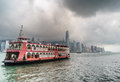 Hong kong harbour with ferry fog clouds during rainy season victoria is a natural landform situated between island and kowloon in Royalty Free Stock Photos