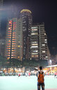 Hong kong sky scrapers and sports playground by night football with people playing march Royalty Free Stock Photos