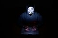 A hooded computer hacker wearing v for vendetta or anonymous mask Royalty Free Stock Images