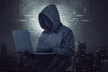 Hooded hacker holding laptop while typing Royalty Free Stock Photo