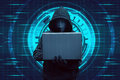Hooded hacker typing on laptop while standing Royalty Free Stock Photo