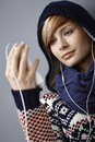 Hooded young woman listening music looking at player Stock Photos