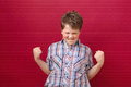 Hooray finally managed boy with power lucky on red background Royalty Free Stock Image