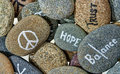 Hope and optimism under every stone symbols words ordain river stones in glass table decoration against white backdrop Royalty Free Stock Image