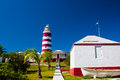 Hope town lighthouse red and white candy cane striped on elbow cay abaco bahamas storage shed with small boat are in the Royalty Free Stock Image
