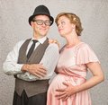 Hopeful pregnant couple man with folded arms and happy female Stock Image