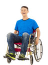 Hopeful young man sitting on a wheelchair in studio Stock Photography