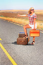 Hoping for a ride blonde beauty wearing shorts thumbing or hitch hiking with suitcase on desolate country road Stock Photo