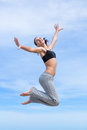 Hopping girl barefoot young woman in short tank top and sporting trousers jumps against the sky Royalty Free Stock Photos