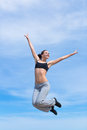 Hopping girl young woman in short tank top and sporting trousers jumps against the sky Stock Photos