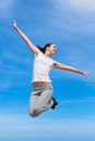Hopping girl young woman in white blouse and sporting trousers jumps against the sky Stock Photos
