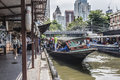 Hopping off the boat passengers are on one of canals klongs in center of bankok in background are scyscrapers of Royalty Free Stock Image
