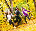 Hopping sisters three on autumnal park and they have a fun together Stock Image