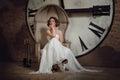 一套婚礼礼服的一个微笑的女孩在奇怪的椅子 一把椅子的新娘在时钟和壁炉工具箱背景 horiz 图库摄影