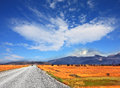 On the horizon are seen snow capped mountains a dirt road pampa car rides a strong wind blows bizarre cloud Stock Image