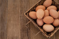 Horizontal of bird eye view of brown eggs in a basket setting on rustic wood slats with space on left for wording Royalty Free Stock Photo