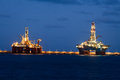 Horizontal oil drilling platforms at night in Cana Stock Images