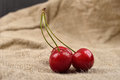 Horizontal photo of tree red cherries with water drops which are together on one green branch on jute on a table. Selective focus. Royalty Free Stock Photo