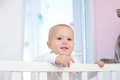 Horizontal portrait of an adorable baby smiling in crib close up Stock Photo