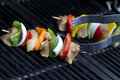 Horizontal shot of tongs grabbing a raw chicken kabob on a grill shallow depth of field Royalty Free Stock Photos