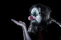Horror clown with ugly face looking to copyspace black backgrou background concept creepy theme party or halloween Stock Photos