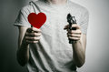Horror and firearms topic suicide with a gun in his hand and a red heart on a gray background in the studio Stock Photography