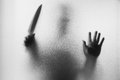 Horror Murderer. Dangerous man behind the frosted glass with a k Royalty Free Stock Photo