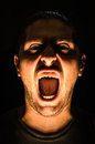 Horror scene with screaming scary human face halloween a harsh light on a black background concept young man open Royalty Free Stock Photos