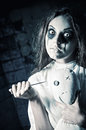 Horror style shot: scary crazy girl with moppet doll and needle in hands Royalty Free Stock Photo